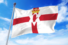 Flag of Northern Ireland developing against a clear blue sky Royalty Free Stock Images