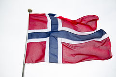Flag of Norway. A Norwegian flag waves in the wind. It features a cross in the middle, as do the other Nordic countries Stock Photo