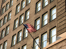 Flag on Old Brick Building. A Flag Flying On The Side of An Old Brick Building Stock Image
