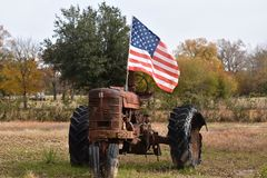 Flag and old Tractor in Gilmer Texas Nov 25 2018. I was driving in East Texas and found this cool sight stock photo
