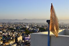 Flag with om hinduism symbol. Orange flag with the Om hinduism symbol. Cityscape of Udaipur town in the morning from roof top and mountain range on a horizon royalty free stock image