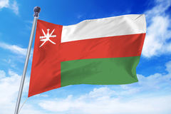Flag of Oman developing against a clear blue sky Royalty Free Stock Image