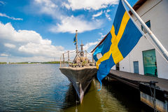 Flag os Sweden blowing in breeze. Blue and yellow flag of Sweden blowing in breese with warship moored in harobour, in background visible blue sky and clouds Stock Photos