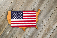Flag over top of United States of America Shape on rustic wooden Stock Images