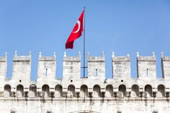 Flag over Topkapi Palace. Istanbul, Turkey - February 5, 2015:A Turkish flag flies over Topkapi Palace and the battlement on a sunny day in Istanbul royalty free stock images