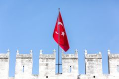 Flag over Topkapi Palace. Istanbul, Turkey - February 5, 2015: A Turkish flag flies over Topkapi Palace and the battlement on a sunny day in Istanbul stock photography