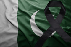 Flag of pakistan with black mourning ribbon. Waving national flag of pakistan with black mourning ribbon Stock Photography