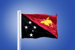 Flag of Papua New Guinea flying against a blue sky Stock Photo