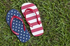 Flag patterned thong shoes in grass Royalty Free Stock Photos