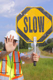 Flag Person Slowing Traffic. A flag person holds up a slow sign to slow vehicles during road construction Stock Photo