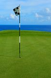 Flag and Pin on Hole Overlooking Pacific Ocean. This is a flag and pin on the tee of a golf course in Hawaii overlooking the Pacific Ocean Stock Photo