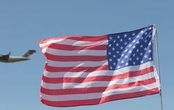 Flag and Plane. Plane flying by the US flag royalty free stock photo
