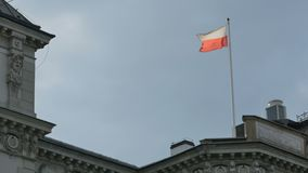 Flag of Poland on Pole. The flag of Poland on  top of building blended in sun stock video footage