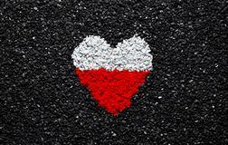 Flag of Poland, polish flag, heart on the black background, stones, gravel and shingle, wallpaper. Flag of Poland, polish flag, sign and symbol, heart on the stock photo