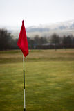Flag pole on golf course scenic green background. Golf course flag pole, with a beautiful scene in the background Stock Photo
