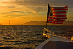 Flag on prow of boat with Golden Gate in distance Royalty Free Stock Photo