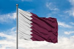 Flag of Qatar waving in the wind against white cloudy blue sky. Qatari flag.  stock images
