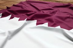 Flag of Qatar on a wooden desk background. Silk Qatari flag top view.  stock images