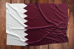 Flag of Qatar on a wooden table background. Wrinkled Qatari flag top view.  stock images