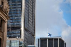 Flag of Quebec waiving in Old Montreal, Quebec, Canada, surrounded by modern office buildings and old skyscrapers. stock image
