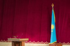 Concept Kazakh official news. Flag of the Republic of Kazakhstan and the nightstand for the speaker on a red background. Without royalty free stock photo