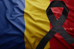 Flag of romania with black mourning ribbon. Waving national flag of romania with black mourning ribbon Royalty Free Stock Image
