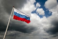 Flag of Russia. Outdoors with dark clouds and sunshine Stock Photos