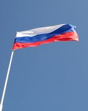 Flag of Russia flapping. Attached to a flagpole flag of Russia flapping in the wind on bl Stock Image
