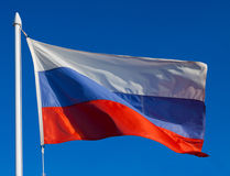 Flag of Russia in flight. Against blue sky during wind Royalty Free Stock Image