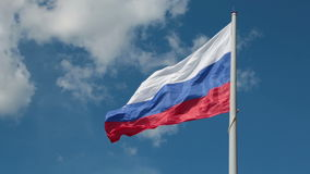 The Flag Of Russia. Russian flag flutters in the wind on the flagpole on blue sky background stock footage