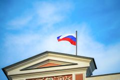 Russian Federation flag. The flag of the Russian Federation on the city hall against the cloudy sky. The wind ripples the flag royalty free stock photo