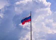 Flag of Russian Federation with cloudy sky on the background. Windy weather royalty free stock images