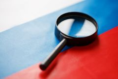 The flag of the Russian Federation looks through a magnifying glass. The study of the history and culture of the people of a large. Country of Russia. The stock images