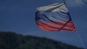 Flag of the Russian Federation. Focus on the lens. Flag of the Russian Federation. The Russian flag develops highly on a wind in slow motion. Close up stock footage