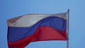 Flag of the Russian Federation. The Russian flag develops highly on a wind in slow motion. Close up stock footage