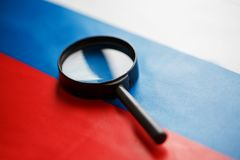 The flag of the Russian Federation is viewed through a magnifying glass. Spying and monitoring Russia. Monitoring the status of. Russian. The concept of the royalty free stock photos
