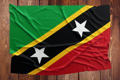 Flag of Saint Kitts And Nevis on a wooden table background. Wrinkled flag top view stock photos