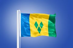 Flag of Saint Vincent and the Grenadines flying. Against a blue sky Royalty Free Stock Image