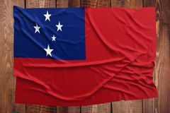 Flag of Samoa on a wooden table background. Wrinkled Samoan flag top view.  stock photography