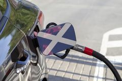 Flag of Scotland on the car`s fuel filler flap. Flag of Scotland on the car`s fuel tank filler flap. Fueling car with petrol pump at a gas station. Petrol stock photos