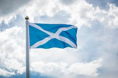 Flag of Scotland in the sky. Flag of Scotland in the wind on a flagpole against a background of clouds in the sky royalty free stock photo