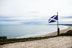 The Flag of Scotland in St Cyrus Beach. Scottish Flag also known as St Andrew`s Cross or the Saltire. St Cyrus Beach, Angus, Scotland, UK royalty free stock photos