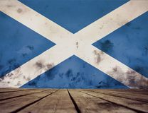 Texture of Scotland flag. The flag of Scotland on a wall of plaster and the wooden floor royalty free stock photography