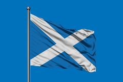 Flag of Scotland waving in the wind against deep blue sky. Scottish flag royalty free stock image