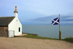 Scottish Flag at St Cyrus Beach, Angus, Scotland. Flag of Scotland and white house. St Cyrus Beach, Scotland, UK royalty free stock image