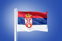Flag of Serbia flying against a blue sky Royalty Free Stock Image