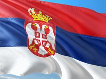Flag of Serbia waving in the wind against deep blue sky. High quality fabric stock photography