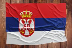 Flag of Serbia on a wooden table background. Wrinkled Serbian flag top view stock images
