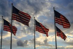 Flag set at sunset , usa. Flag set at sunset, sky, clouds, sun, colors, waving, red stripes, stars royalty free stock image