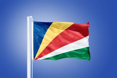 Flag of Seychelles flying against a blue sky Stock Photo
